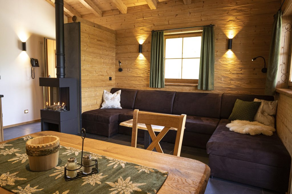 große Almhütte mit großer Couch und Gaskaminofen